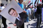 Syria's Presidetn Bashar Al-Assad, seen in the portrait being held by a supporter in 2010, has been accused of using sarin gas against his own people, sparking a debate on U.S. intervention. (Photo by Beshroffline, via Flickr)