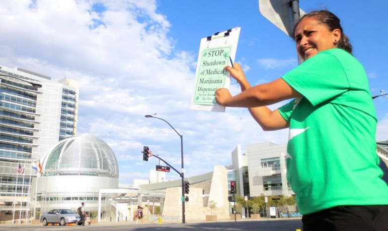 Anita Inocencio, whose mom relied on edibles to ease the pain during chemotherapy for lung cancer, stands across from City Hall trying to drum up signatures for a referendum.