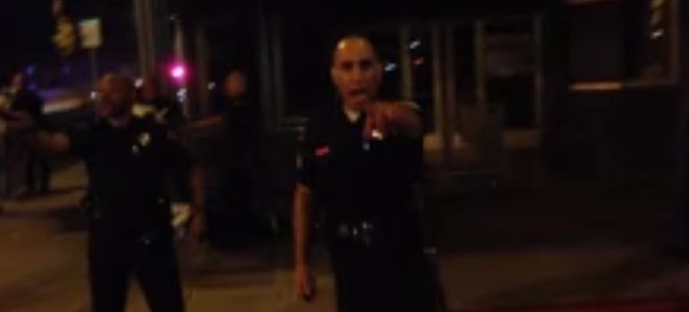Grainy cellphone footage shows a man getting roughed up by police as officers attempt to control the scene.