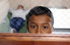 A young boy looks out the window of his room in a Texas holding center. (Photo by Eduardo Perez, via U.S. Customs and Border Protection)