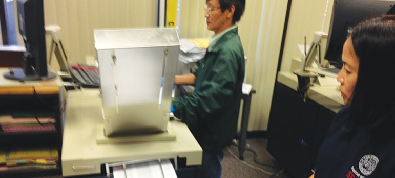 Fourteen machines inside the county Registrar of Voters take stacks of ballots and spit them out rapid-fire for results.
