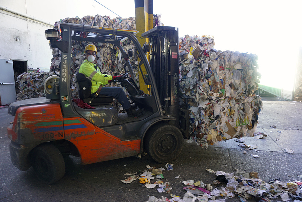 A CWS worker moves bales of recyclables, which end up getting shipped to China.