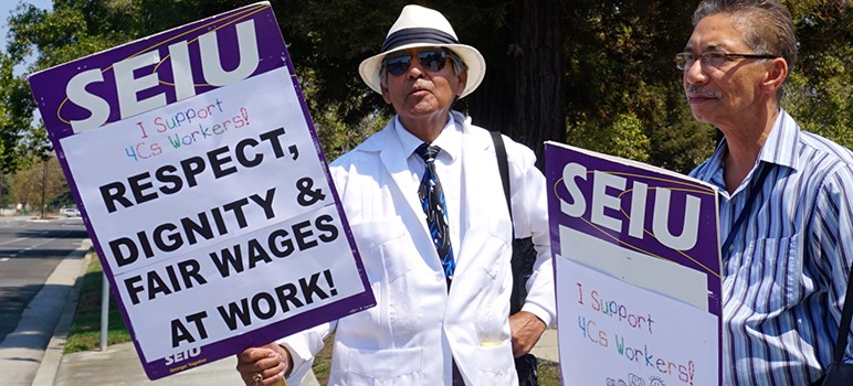 4Cs Council employees Mario Del Castillo and Fred Brion picket outside the nonprofit's north San Jose headquarters.