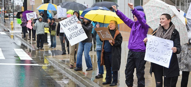A downpour of rain Monday didn't dissuade anti-Trump protesters from coming to San Jose City Hall. (Photo by Benjamin Siepak)
