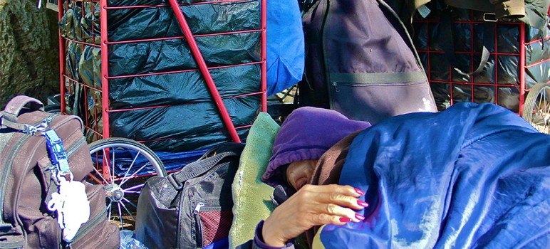 A homeless woman in San Jose sleeps among her belongings. (File photo by Chip Scheuer)