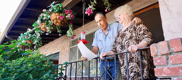 From the front porch of their aging duplex, Dick and Helen Kavanagh review one of countless apartment applications they've had to fill out. (Photo by Jennifer Wadsworth)