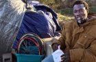 Sharwian Bobian sits outside his makeshift shelter.